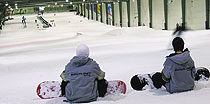 Snow boarders resting at the top of the 200 metre long slope inside Snow Planet
